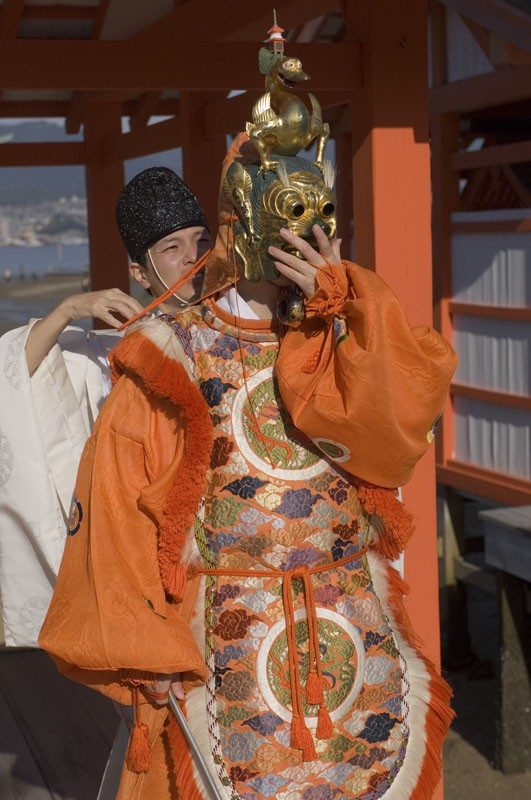 A Shinto priest helps a dancer put his mask on.