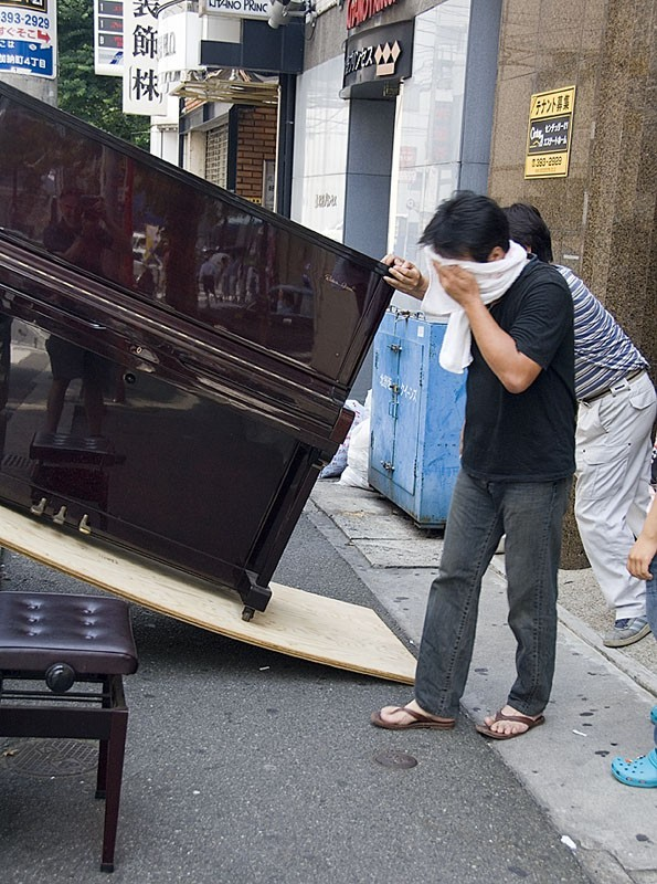 People trying to move a piano.