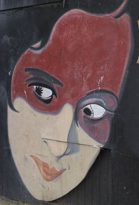 A red lady painted on a building.