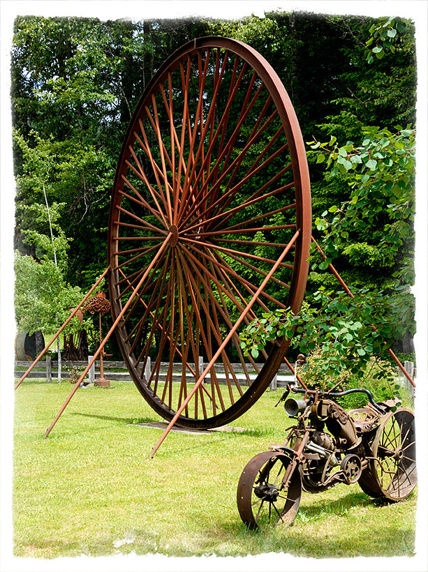 A giant wheel sculpture made of scrap iron.