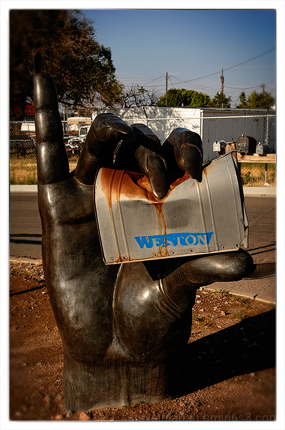 A bronze hand holding a mailbox in Santa Fe, NM.