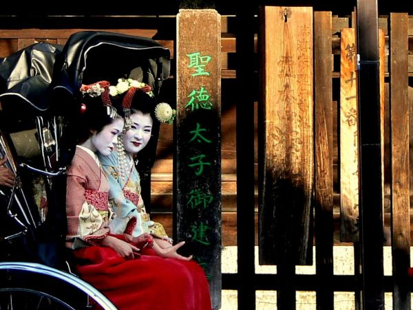 Japanese maiko (apprentice geisha) in a rickshaw