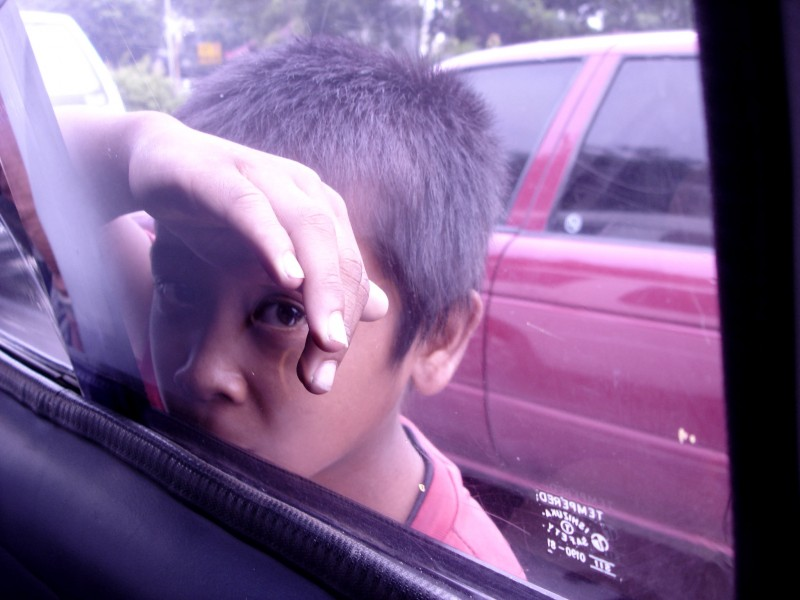poor kid looking through car window