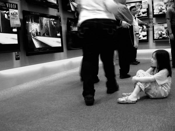 a little girl sitting on floor watching advert