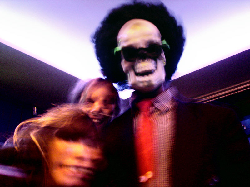 two girls hanging out with a afro guy with mask