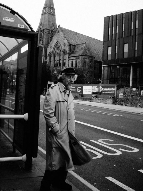 old man waiting for bus in cold weather