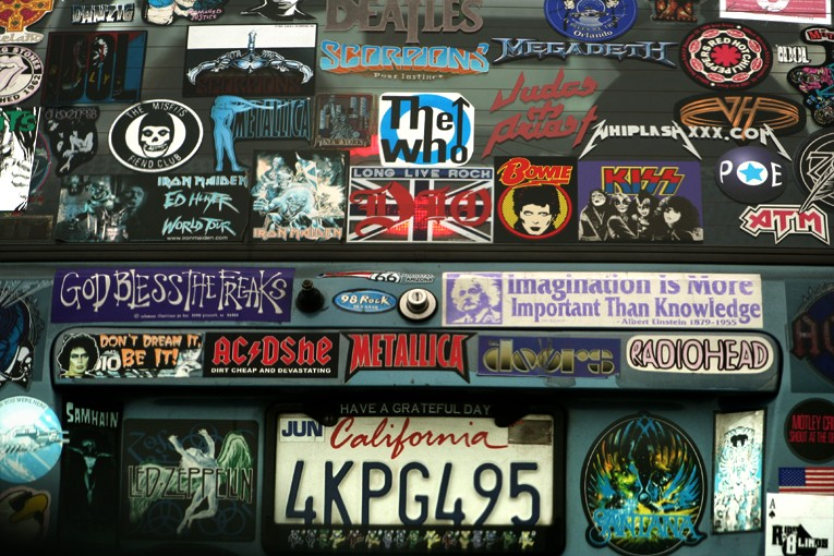 car covered with rock and roll bumper stickers