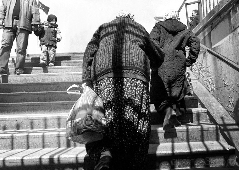 Child watches two old ladies walk up steps
