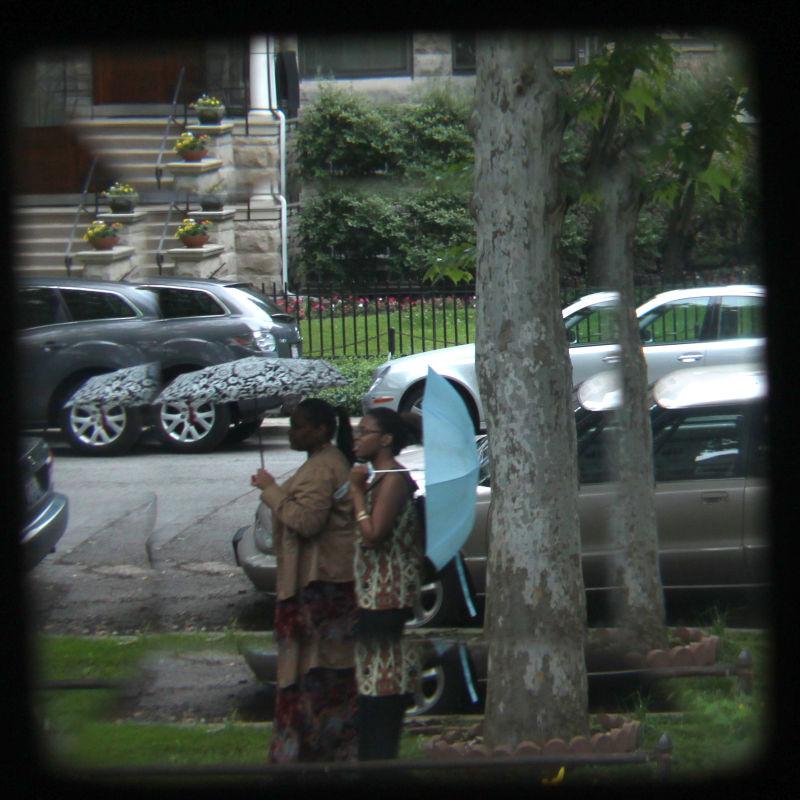 Two women carrying umbrellas seen through window