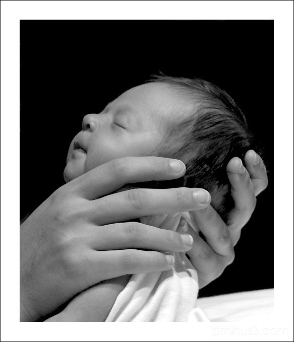 Portrait of a baby in her mother's hands.