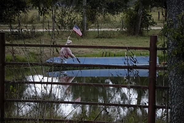 Pond, boat, man and flag, near San Antonio
