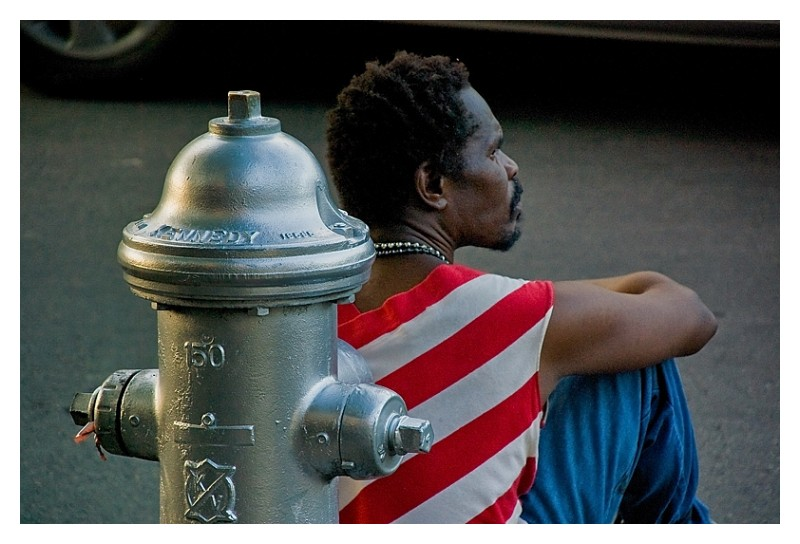 Man in red & white stripes sitting against hydrant