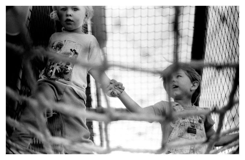 Friends holding hands on play net