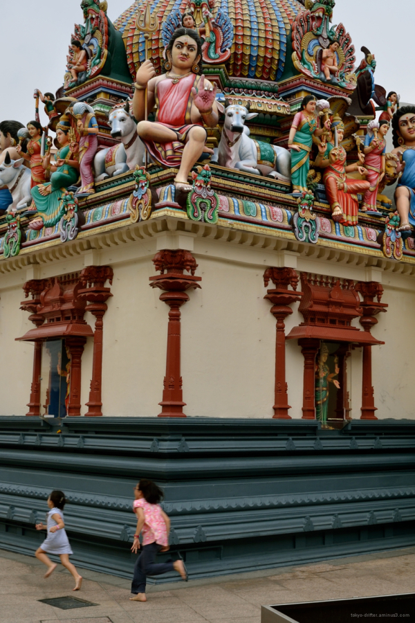 Two children chase each other about a Hindu Temple