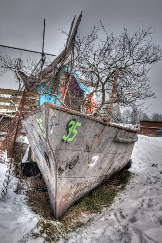 An old boat in the snow, in the city of Amsterdam