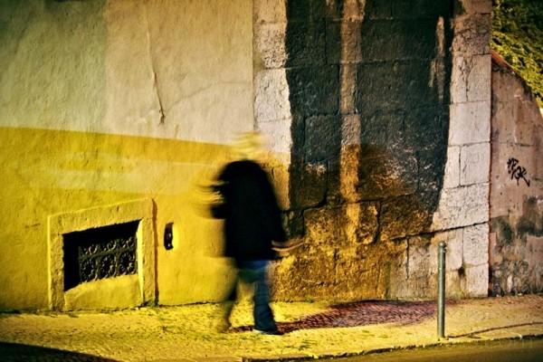 man walking in the street at night