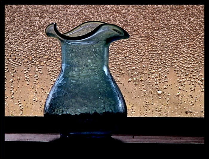 Blue vase in a window with condensation.