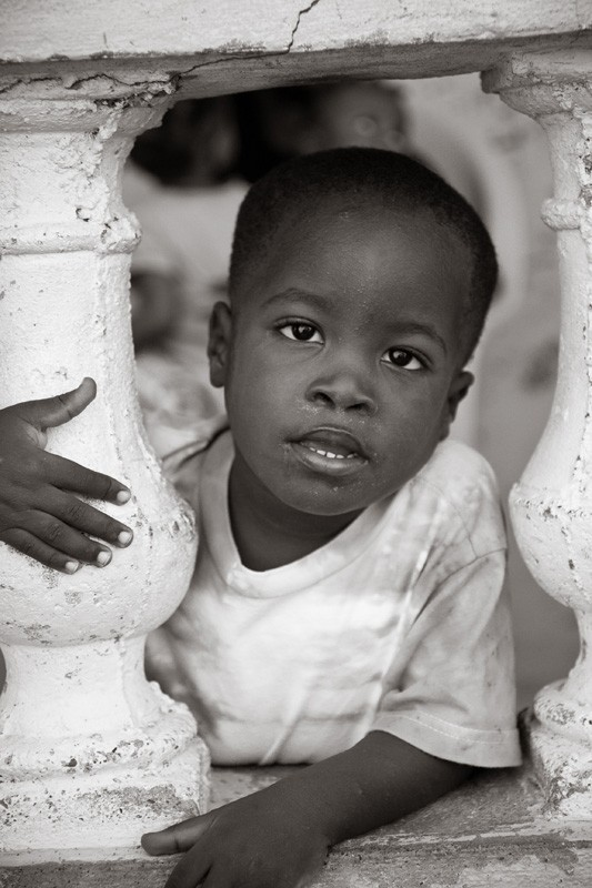 Haitian boy looking through concrete porch