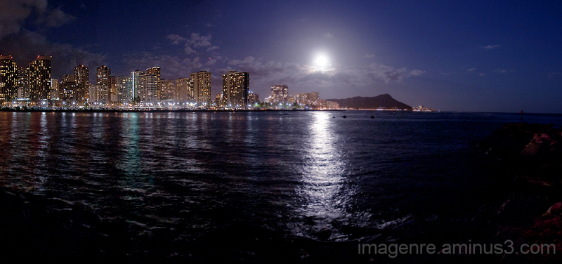 Honolulu, United States, Waikiki is one of my favorite places to photograph in Hawaii.  This image was made for the latest theme.  I went to Magic Island and shot back towards the full moon over Waikiki.  Diamond Head crater is also in the image.  To the right foreground is a rock outcropping of Magic Island, helping to give depth of field to the image.  That night was the night when the full moon was closest to earth for the year.  There were probably twenty photographers lined up along the edge of Magic Island to capture the moment when the moon broke through the clouds.  This was my best effort for the evening.