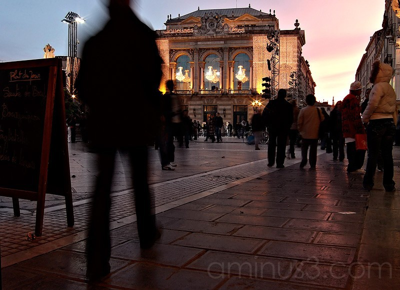 People walking in the Comedie at dusk.