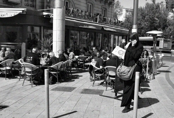 Woman walking by a cafe in Montpellier, France.