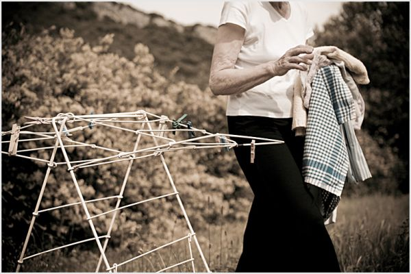 A woman gathering laundry off a rack.