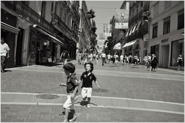 Two young boys running in the street.
