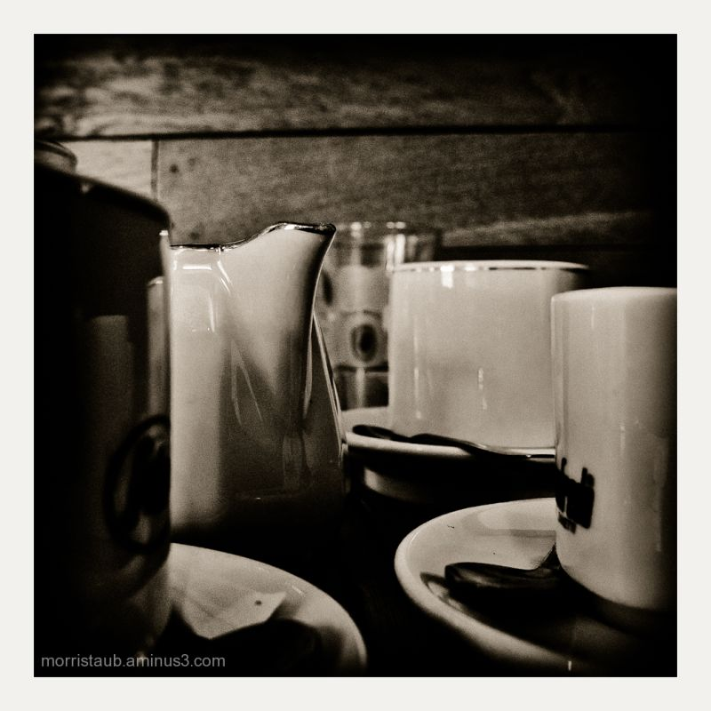 Coffee cups and milk on wood table.