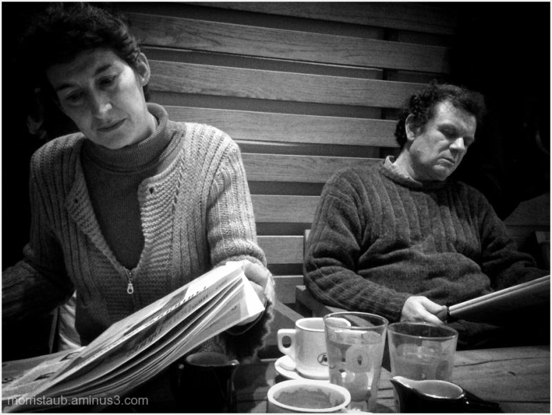 Two people reading newspapers in a cafe.