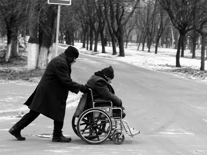 An old man being pushed in his wheel chair.