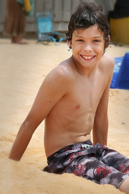 boy sitting in sand at beach