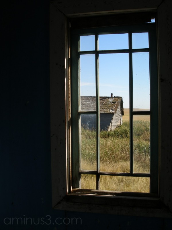 A barn through the window of abandoned farmhouse