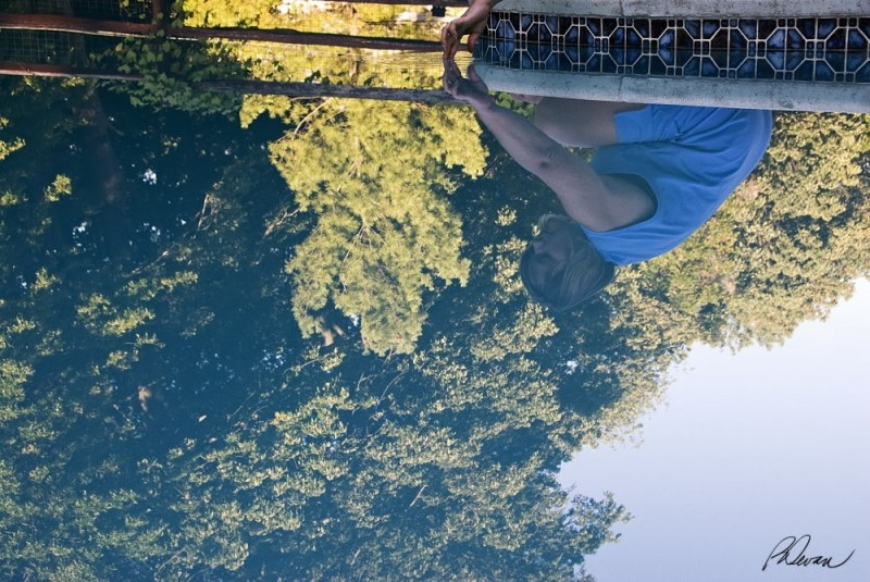 reflection of woman sitting beside swimming pool