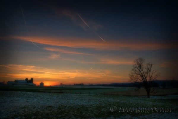 snow-covered farm field at sunset