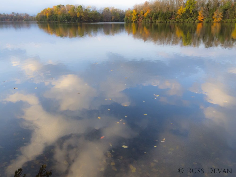 Clouds and autumn leaves reflected in water