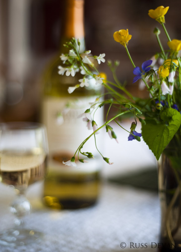 a glass and bottle of white wine with wildflowers