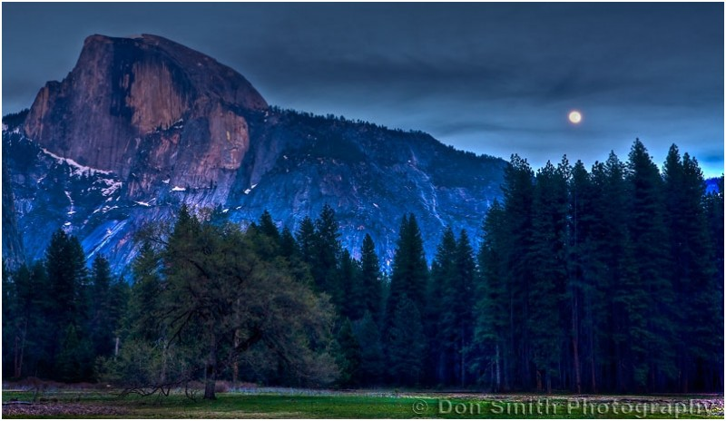 A full moon rises near Half Dome in Yosemite.