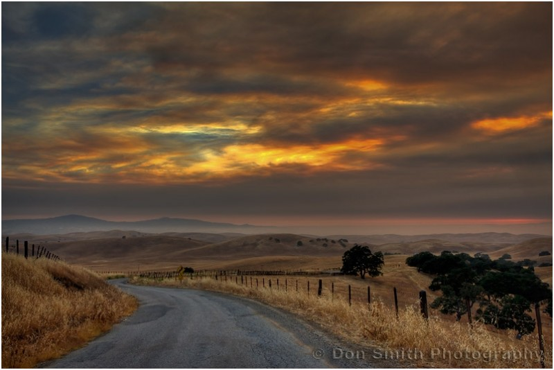 A country road leads towards a sunset sky.