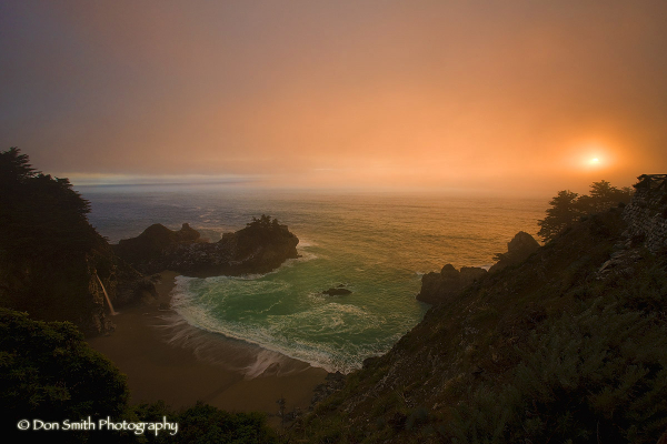 Sunset through fog on McWay Falls in Big Sur.