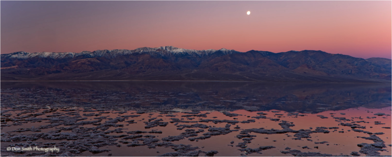 A full moon sets at sunrise in Death Valley.