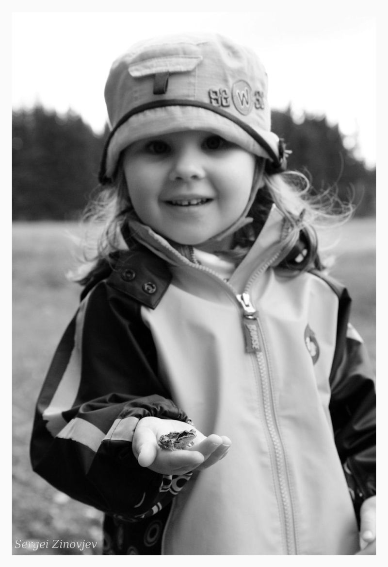 little girl holding a frog in her hand