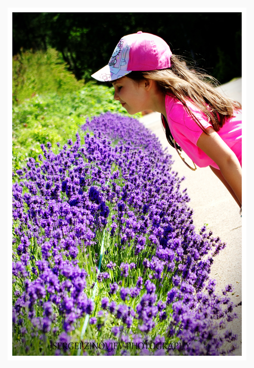 girl smelling purple flowers