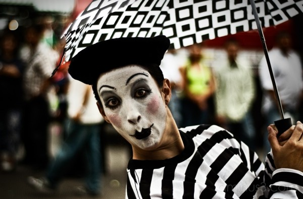 A mime makes a kind gesture.