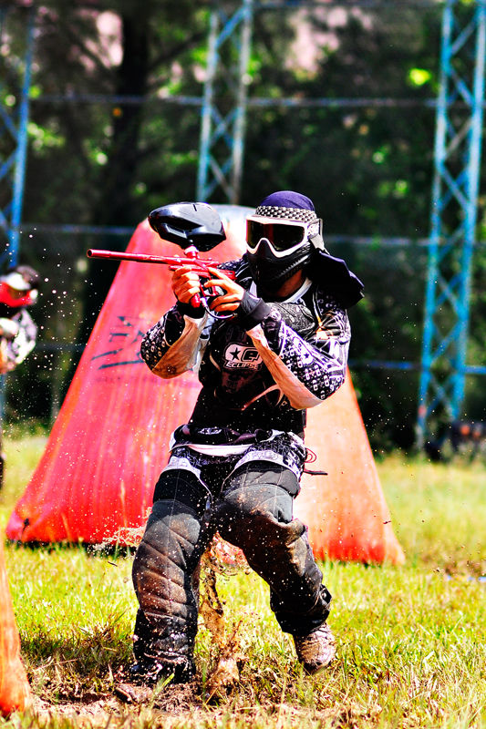 A paintball player hitting the mud