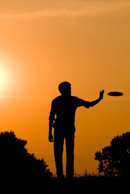 playing frisbee at sunset