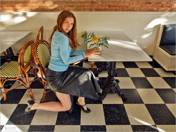 Jesse seaated at the table blackleather skirt