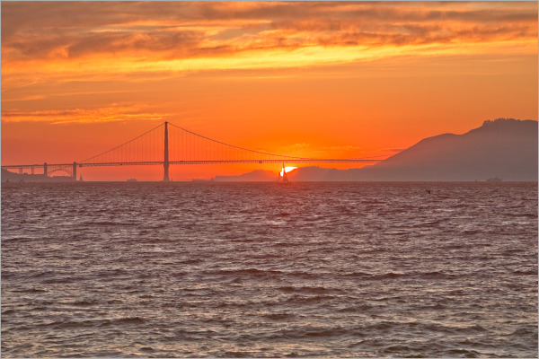 sailboat across The Golden Gate at sunset