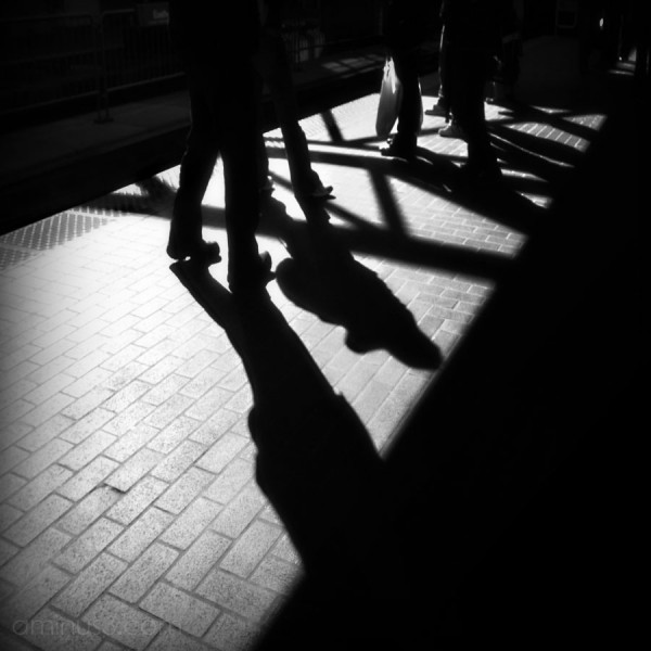 shadows of people waiting at train station