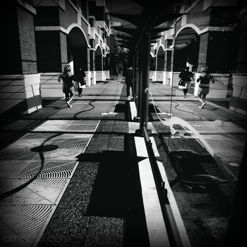 reflection in busstop of people walking