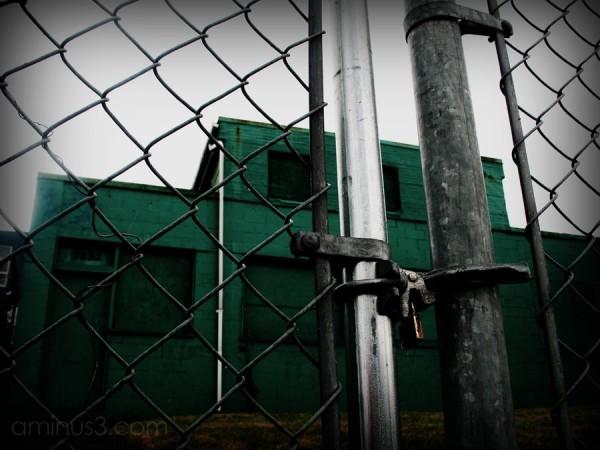 abandoned building behind locked fence